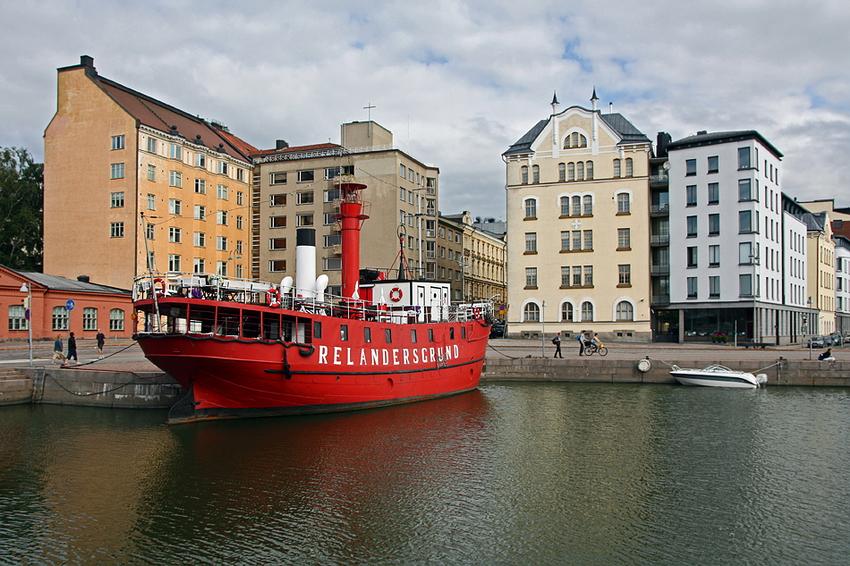 Fotografia do barco ancorado na margem, tendo por detrás a rua com algumas pessoas e como fundo um conjunto de belos edifícios