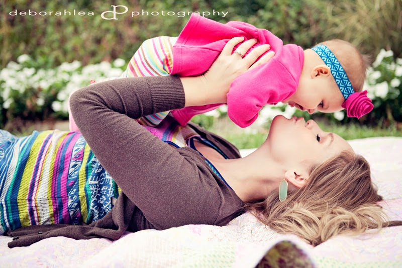 This mom is laying down while holding up her baby and giving her a big kiss at the  Botanic Gardens.