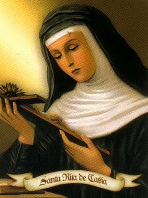 Santa Rita mirando un crucifijo que sostiene en las manos.