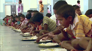 Indian children eat a school meal