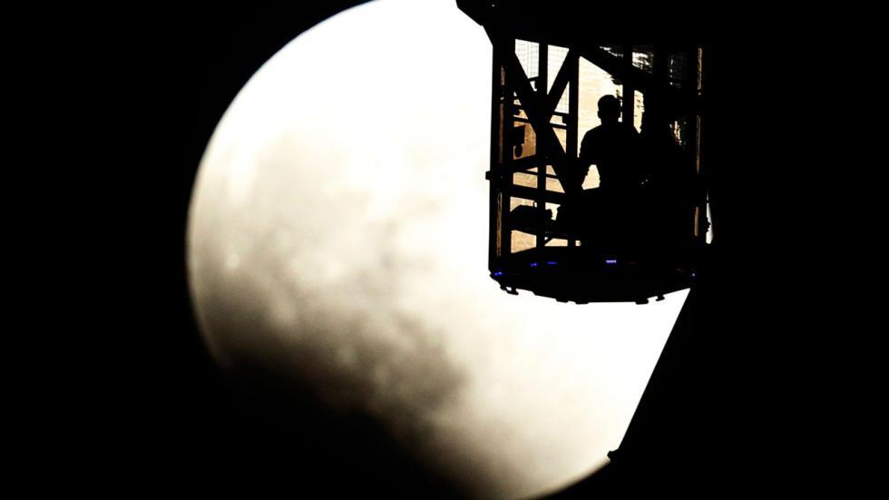 Пара на колесе обозрения наблюдает, как тень Земли начинает накрывать Луну