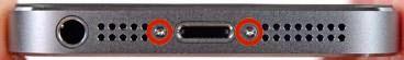 quitar tornillos a ambos lados del conector de carga del iphone para desarmar el teléfono