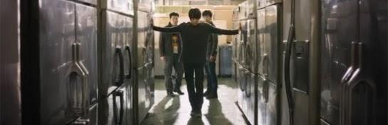 Kim Joon walks down a line of freezers as Choon Dong and Yang Soo, played by Lee Joon Hyuk 이준혁, watch.