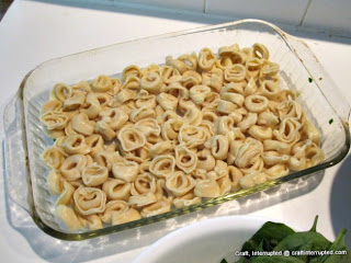 Step one is to layer cooked tortellini on bottom