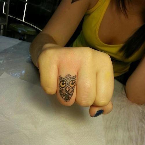 chica con tatuaje de buho en el dedo