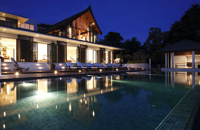 Photo of modern villa at night as seen from the pool