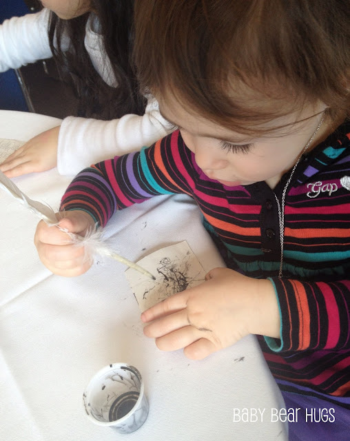 young child writing with a quill and ink