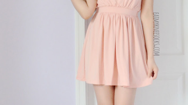Close-up of the hem on the pastel pink WalkTrendy chain halterneck dress.