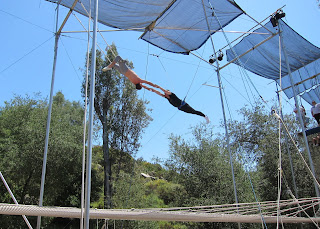 Noah in a knee hang grab on the flying trapeze.