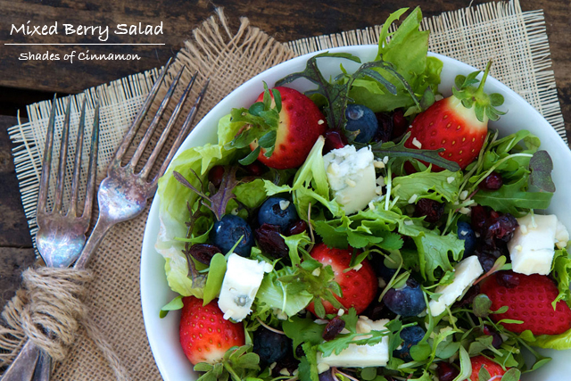 Mixed berries in a salad of baby greens with cheese and nuts