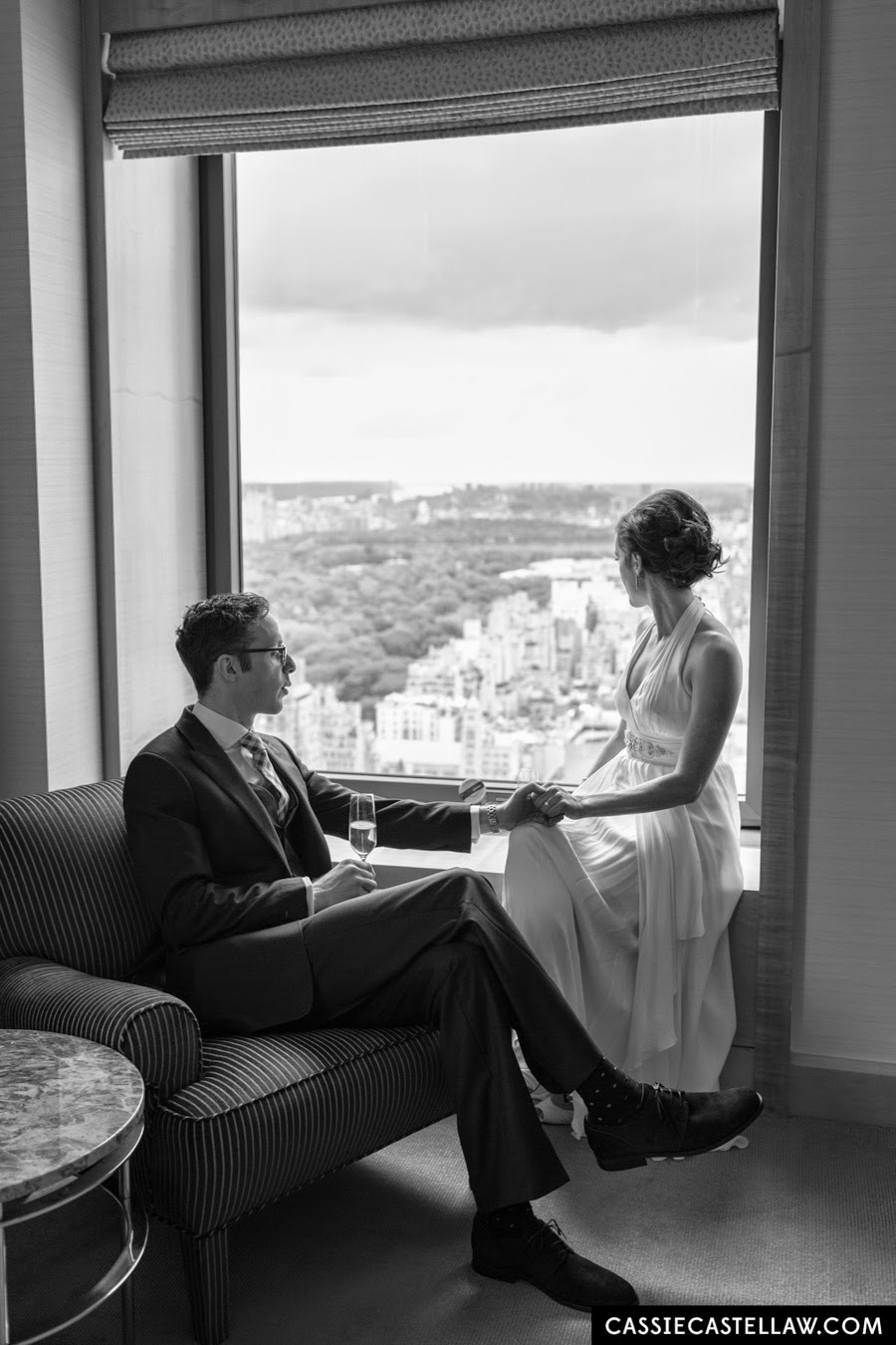 black and white portrait of bride and groom sitting by window overlooking Central Park. NYC Lifestyle wedding photography by Cassie Castellaw. www.cassiecastellaw.com