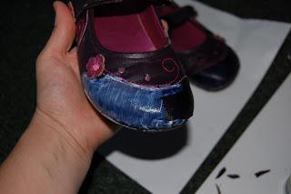 decoupage ragasztót kentem a cipőre, rátettem az anyagfoltot, majd ezt is lekentem ragasztóval. A képen a cipő orrára van ráragasztva a lila folt. Egyik felén ragasztós, másikon nem. A ragasztós fele kék színben játszik, a másik mélylilán.