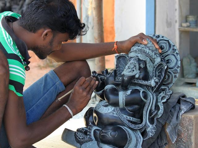 индус за работой, вырезает скульптуру из камня