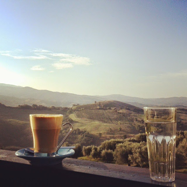 Two glasses with water and cappuccino and the view over the Tuscan hills