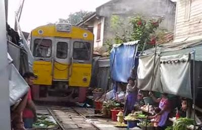 Στην αγορά Mae Klong οι άνθρωποι ψωνίζουν πάνω στις ράγες του τρένου