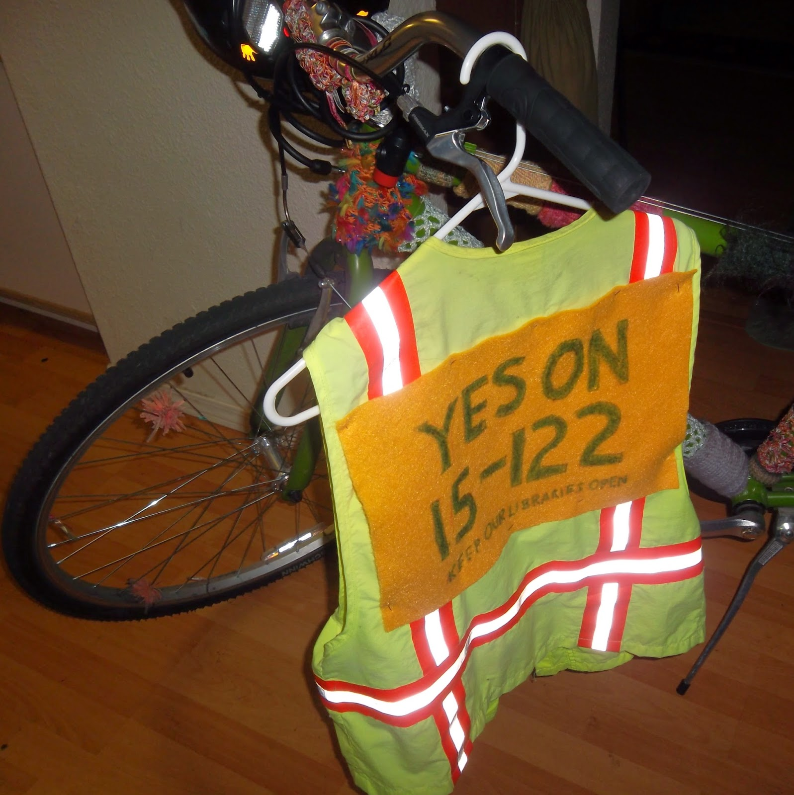 "Reflective vest on hangar, hanging from the handlebar of my bicycle. A sign pinned to the back of the vest reads ""YES ON 15-122"" in large green letters against a gold background. Smaller letters, also green, along the bottom read ""KEEP OUR LIBRARIES OPEN."""