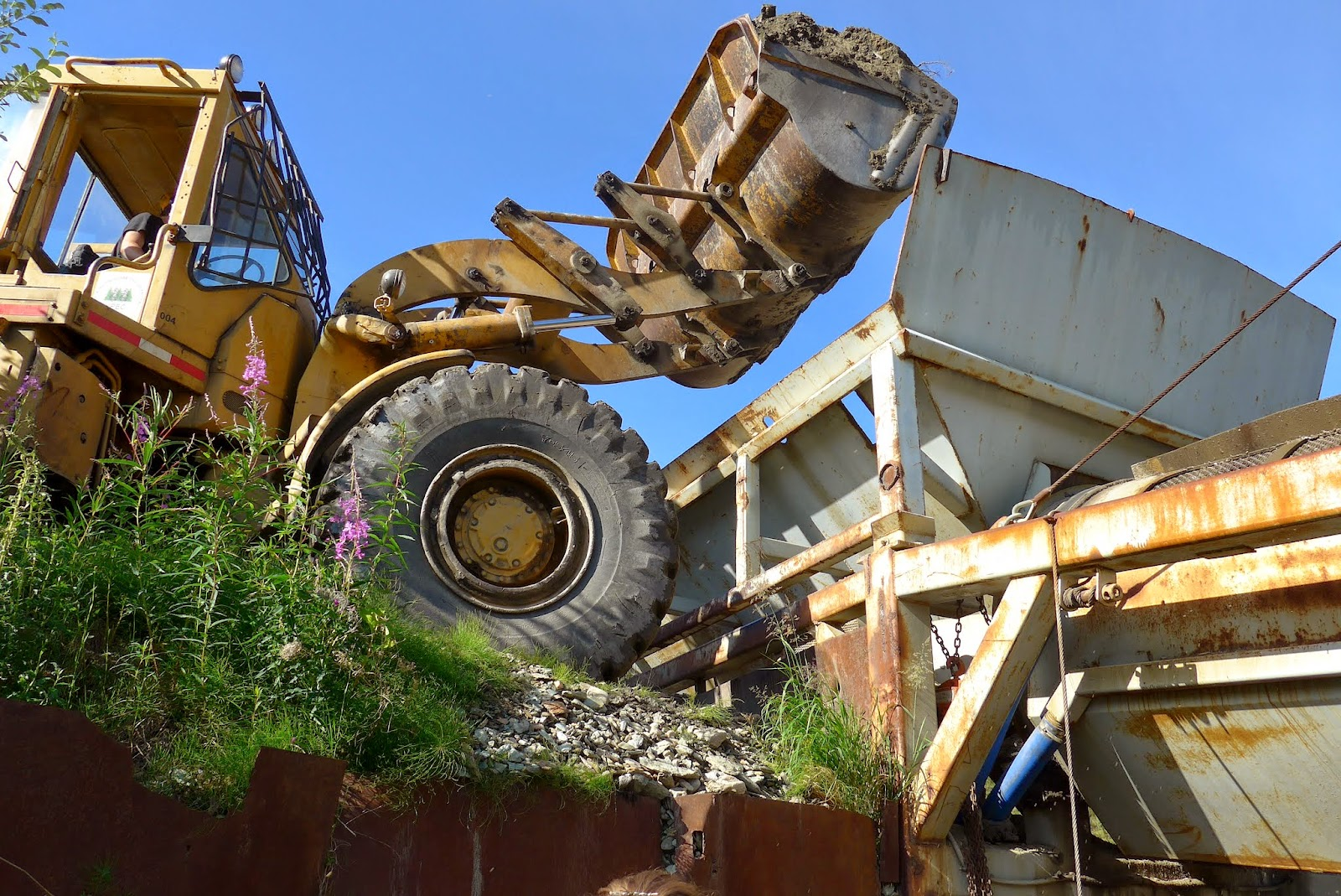 Large front loader dumping dirt into the large sluice.