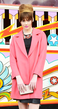 Model on shoot for magazine wearing a pink coat with an elegant bun hairstyle