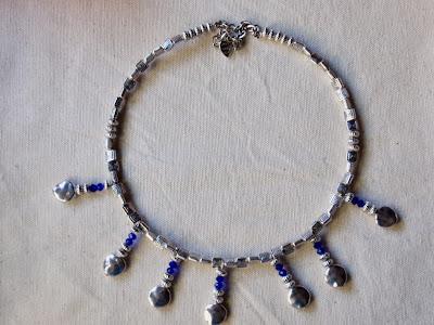 gargantilla artesanal elaborada con abalorios pequeños con dibujo de cuadrado y colgantes elaborados de cristales azules y abalorios martilleados planos