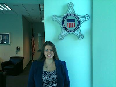 Ph.D. Student Weiss stand below a replica of a U.S. Secret Service badge.