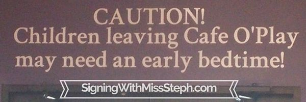 """Sign above the door reading """"children leaving Cafe O'Play may need an early bedtime!"""