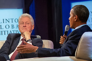 Photo of President Bill Clinton and President Barack Obama discussing health care at the 2013 Clinton Global Initiative.