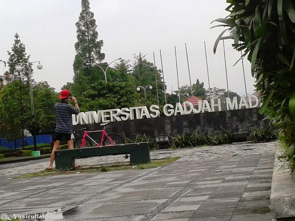 """Salah seorang pesepeda berfoto didepan tulisan """"Universitas Gadjah Mada"""""""