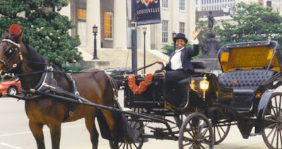 a horse and carriage and driver waving in downtown louisville with a building in the background
