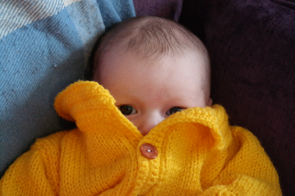 Baby vanishing into yellow cardigan