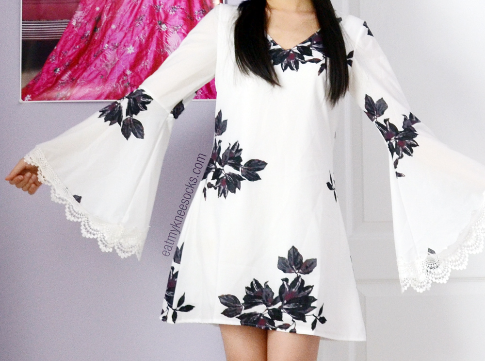 JollyChic's dupe on Free People's Wanderer mini dress in white, with bell sleeves, lace trim, and a shift body.