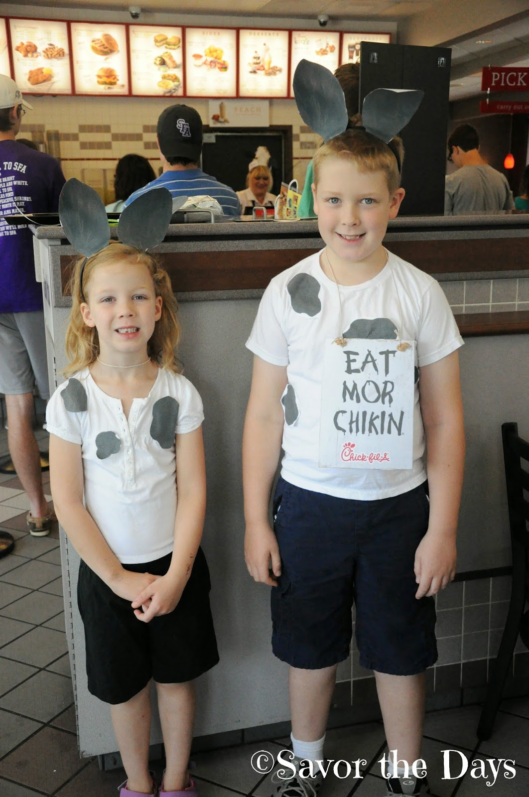 2 kids dressed like cow for Chick Fil A cow appreciation day
