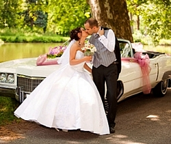 Bride and groom with vintage wedding car