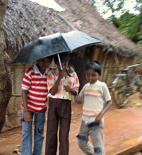 kids sharing an umbrella