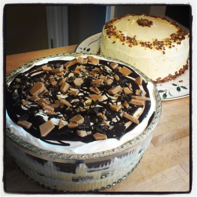 Photo of large, round trifle composed of three layers of brown cake, yellow custard, white whipped topping, and brown ganache, with toffee on top. Behind it is a two-layer cake covered in white icing and decorated with crumbled pecans.