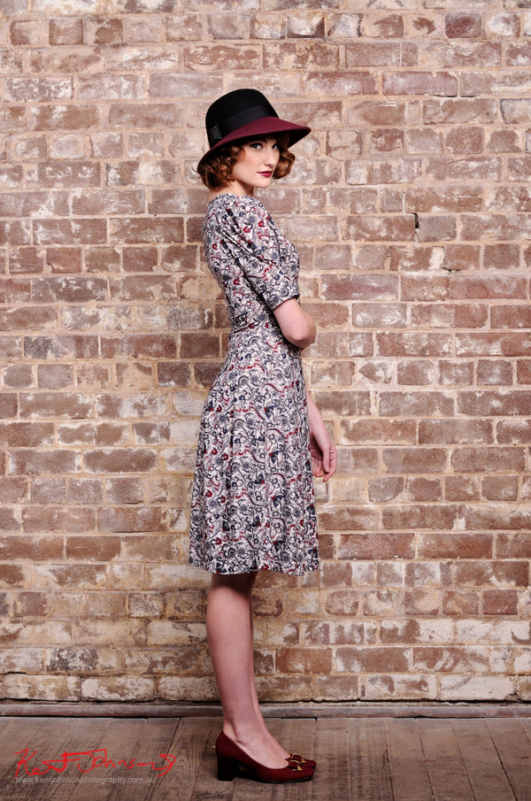 White Red and Navy Blue 40's style dress worn with soft two tone felt hat photographed full length and in profile against a distressed brick wall in the studio - studio fashion photography