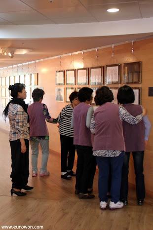Señoras coreanas admirando los bordados budistas