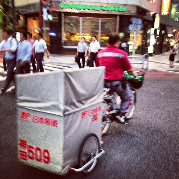 A post office delivery bicycle pulling a trailer.