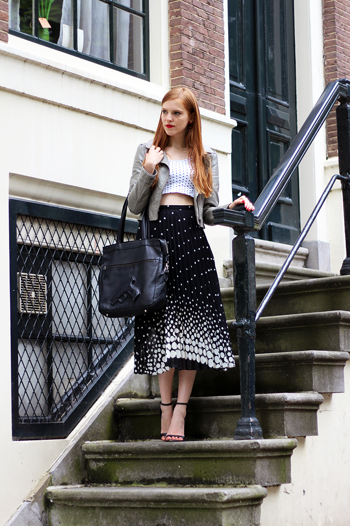 Vintage fashion blogger outfit with polka dots, pleated midi skirt and gun bag