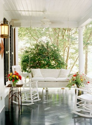 This white-themed front porch decor looks fresh against the dark wood stained deck and gorgeous greenery