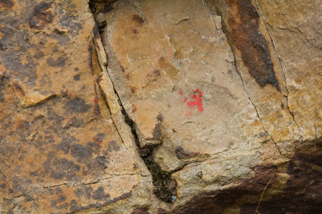 faded red arrow on rock