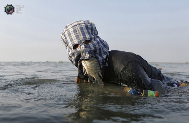 Рыбак ищет сеть в озере Лагуна-де-Бай в городе Тагиг, Филиппины. (Cheryl Ravelo/REUTERS)