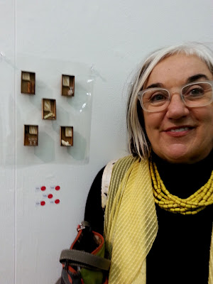 A woman stands in front of five miniature brooches on display in a gallery, with five red dots underneath.
