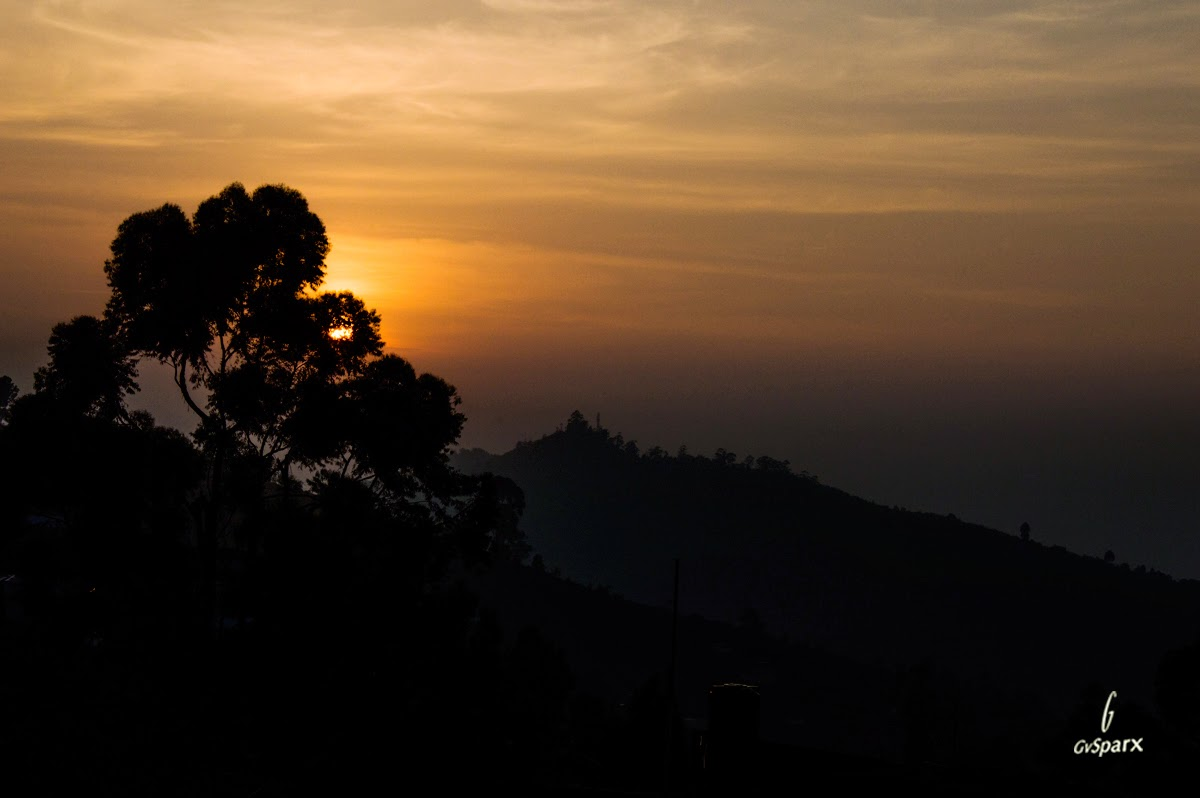 Sunrise, behind the trees and hills in kodaikanal