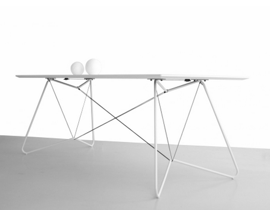 A combination of gray tubes and strings hold white laminated dining room table together