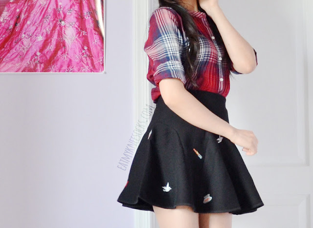 A cute, Korean fashion inspired fall outfit featuring a red plaid shirt and a black flared high waisted embroidered skirt/skort from Brandedkitty Shop.