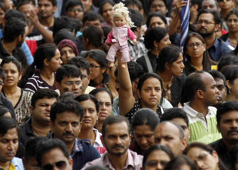 A parent holds high a doll belonging to her child as she participates in a protest against alleged police inaction after a six-year-old was raped at a school, in Bangalore, India, Saturday, July 19, 2014. More than 4,000 parents and relatives of children who attend the school shouted slogans against the school's administration Saturday and demanded that police arrest those involved in the July 2 incident, which was reported only this past week.