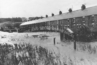 A black and white photo of a row of houses flooded to the doors, the gardens covered and the tops of fence posts visible above the waters.
