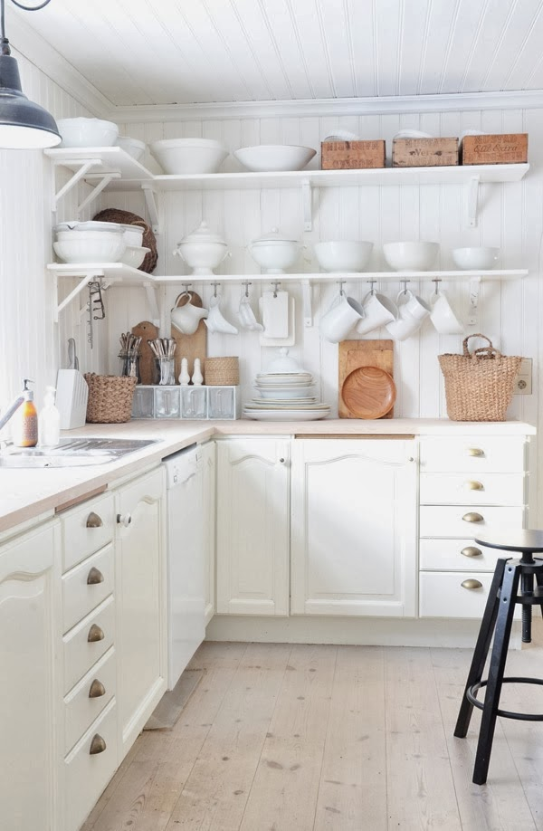 White kitchen with open shelving and natural wood and woven accents