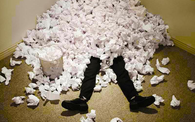 Na imagem de capa: Uma pessoa enterrada em uma pilha de bolinhas de papel amassada, apenas as pernas de calça preta para fora. Também saindo do papel uma lata de lixo cheia.