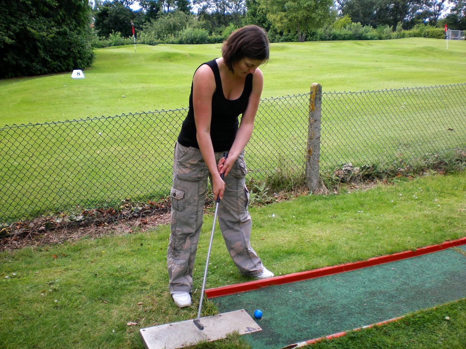 Emily playing Crazy Golf in Luton's Wardown Park in July 2007. The very green grass putting layout is on the other side of the fence